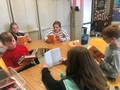 students sitting at a table reading books