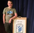 student standing next to art for autism sign