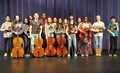 students standing on a stage with orchestra instruments