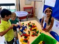 students building a dog house with legos