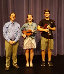 two students holding a violin and viola with orchestra director