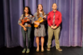 two students with violin and viola standing with director