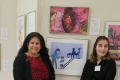 teacher and student posing by artwork