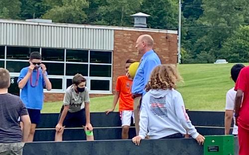 principal playing ball with students