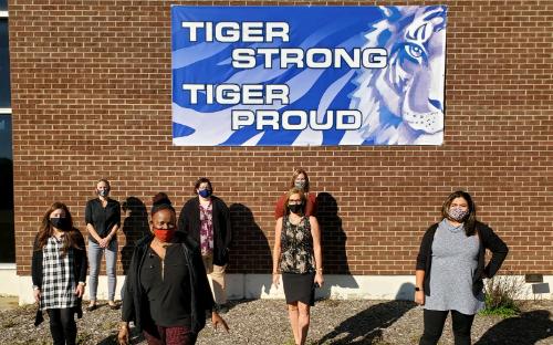staff standing in front of school