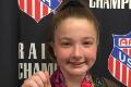 student gymnast holding medal