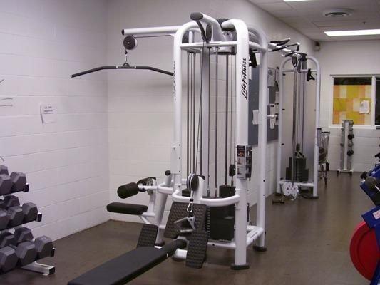 A row machine and lat pull down machine in the high school weight room