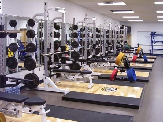 6 racks lined up in front of the mirrored wall in the high school weight room