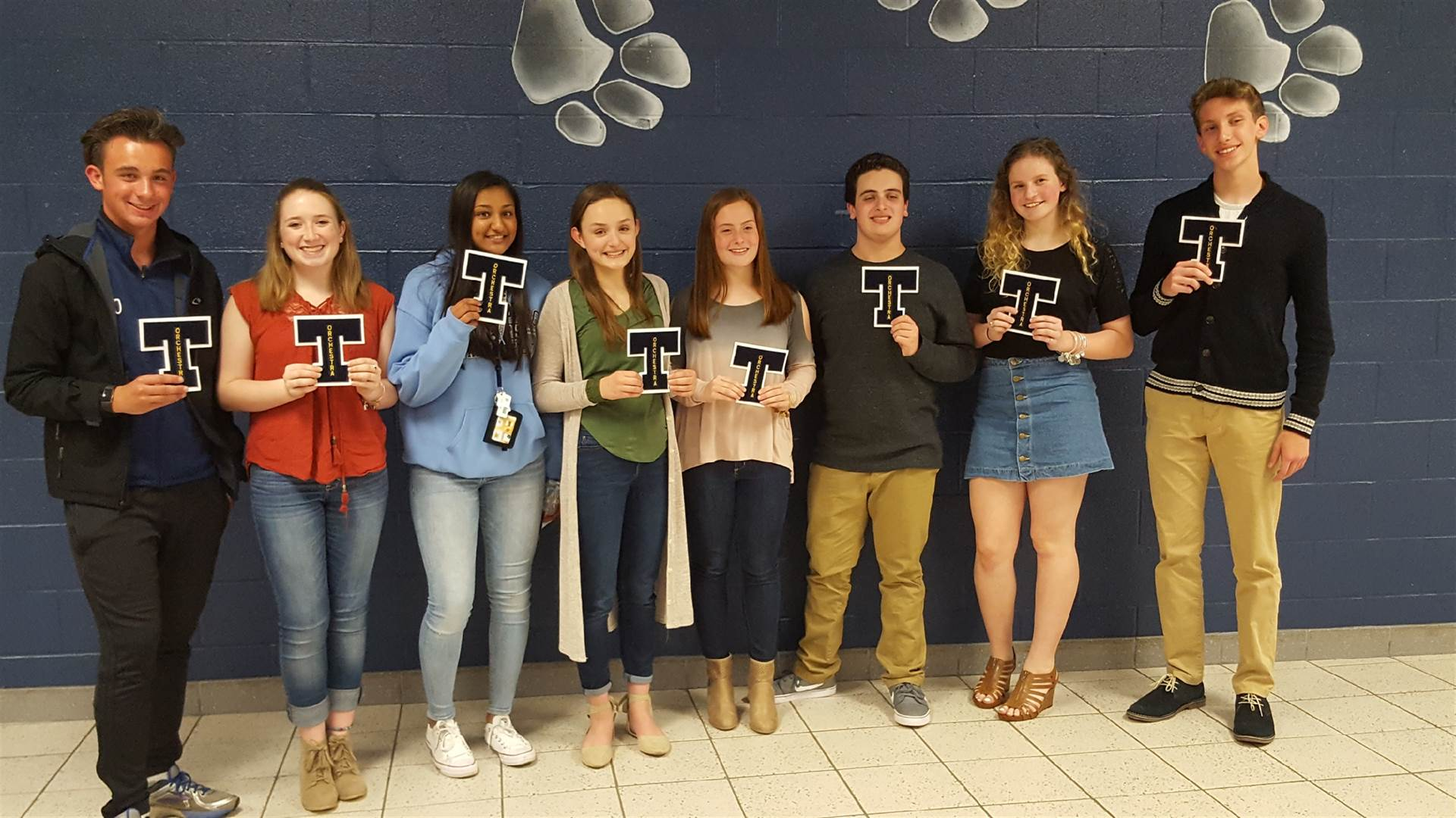 Some orchestra letter winners holding their letters.