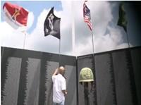 Man in front of replica of Vietnam Memorial Wall