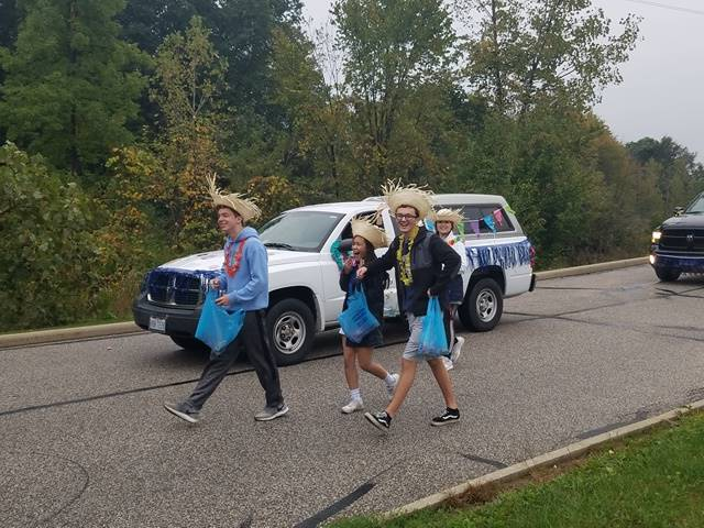 students wearing straw hats walking next to decorated SUV in parade