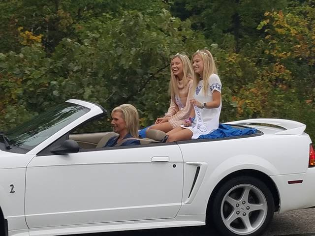 Students riding in the back of a convertible
