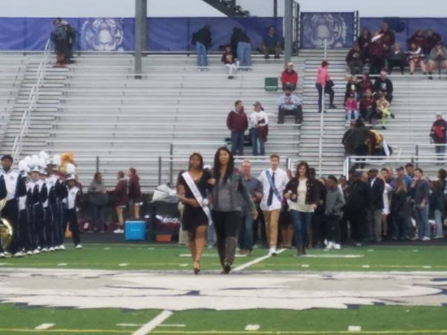 Student and parents walking across football field