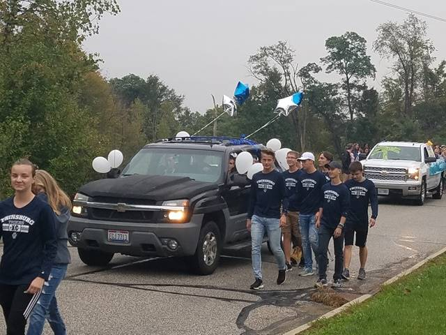 Students walking in parade next to SUV