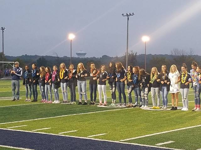 Homecoming court standing on football field