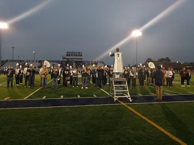 Marching band performing on football field