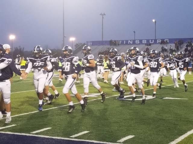 football team running on the field