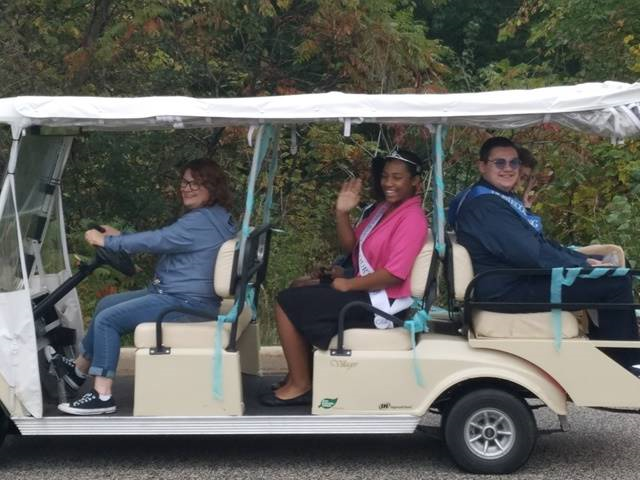 Students and driver sitting in golf cart