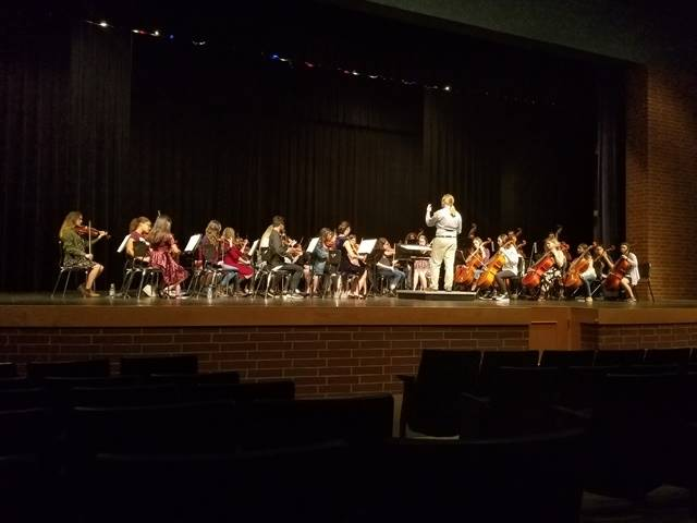 Students performing in an orchestra on a stage