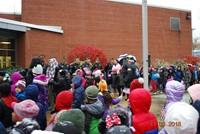 Flag ceremony honoring veterans outside of school building