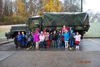 Students and teacher in front of military vehicle