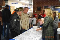 Military veterans checking in at table to enjoy school celebration of veterans