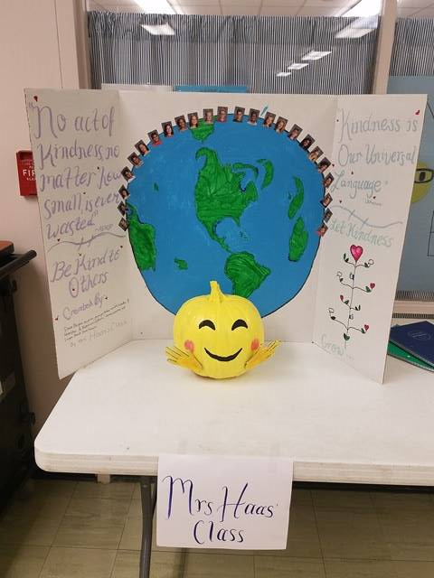 pumpkin painted yellow in front of picture of the world