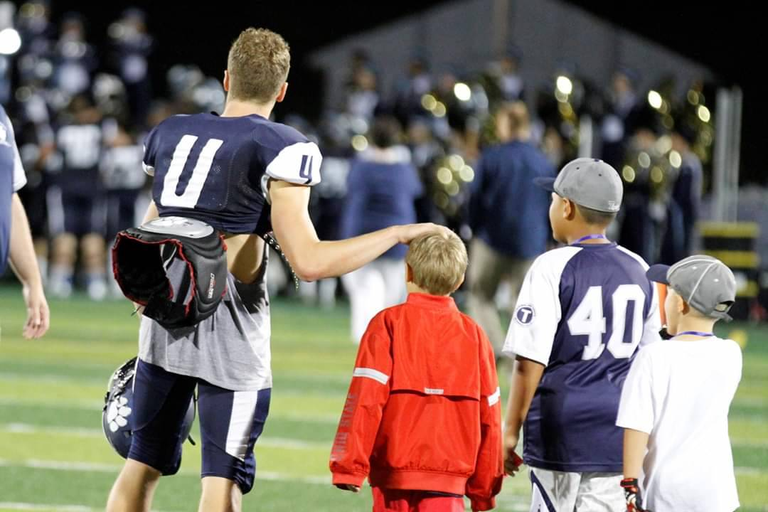 The QB hanging out with the ball boys after the game.