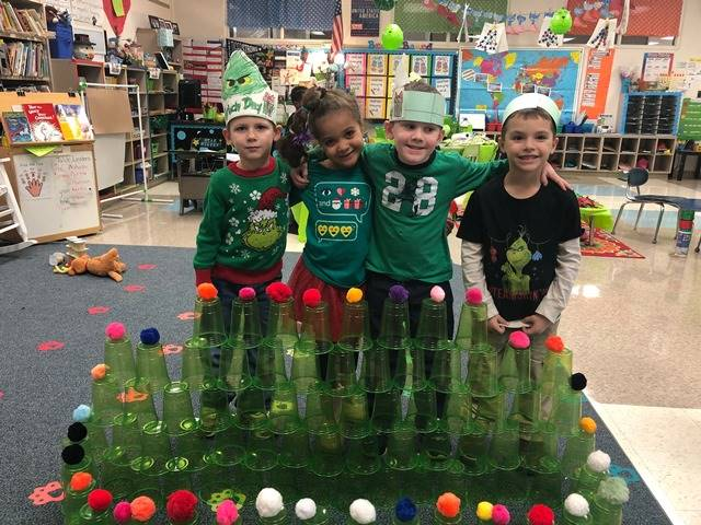 Students standing in front of a pyramid of green plastic cups