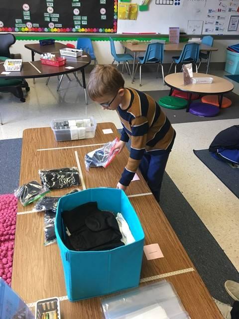 Student putting socks in ziploc bags