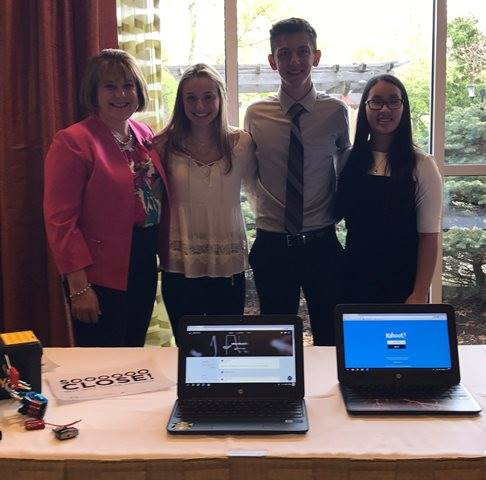 Superintendent and three students in front of Chromebooks