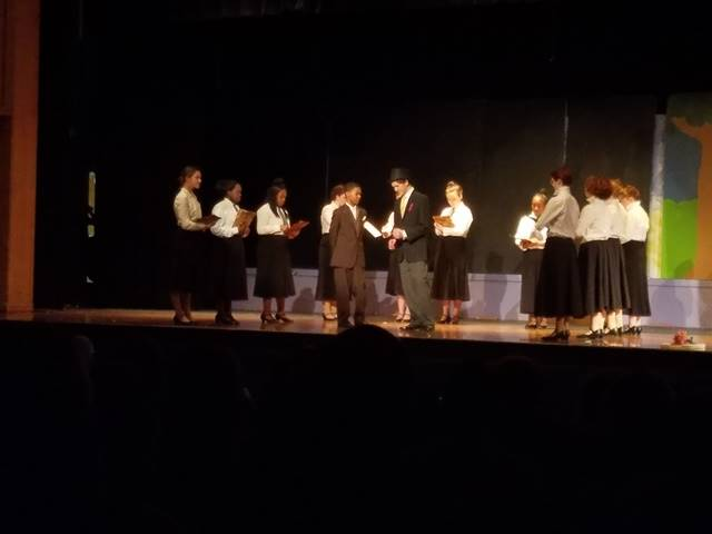 Students performing in a play on stage