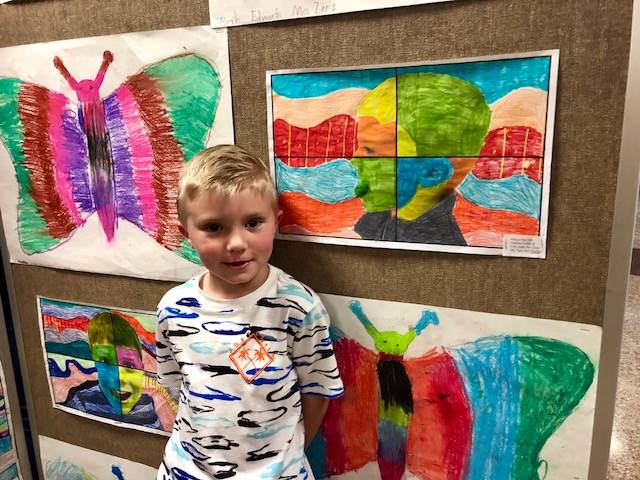 Student standing next to his artwork