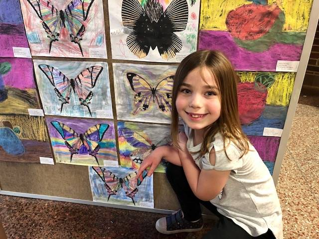 Student squating near her artwork