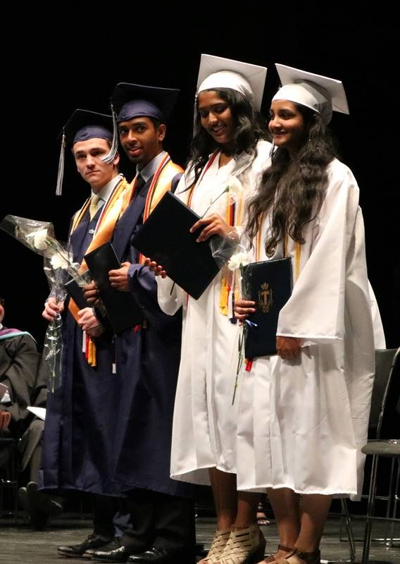 Group of four graduates holding diplomas and flowers