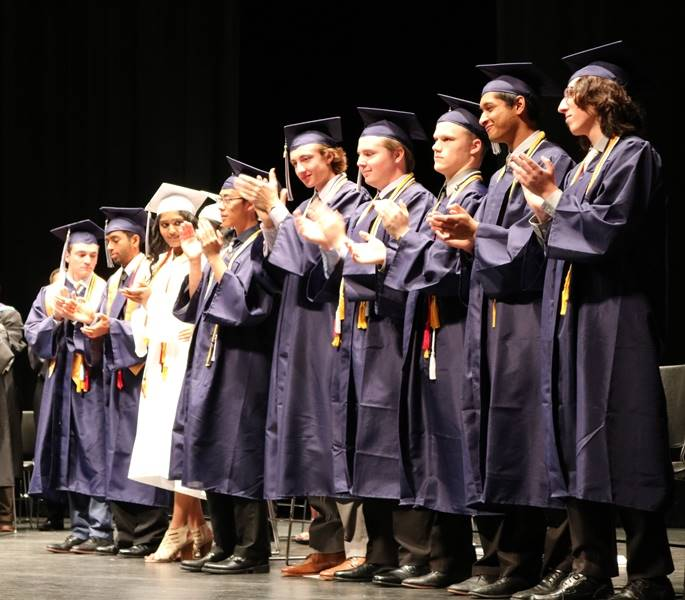 Ten graduates on stage clapping