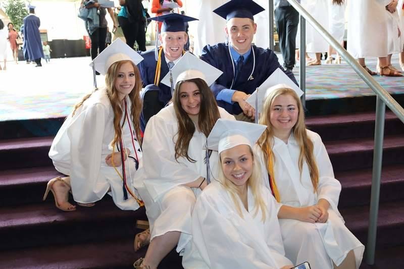 Group of six graduates sitting on stairs