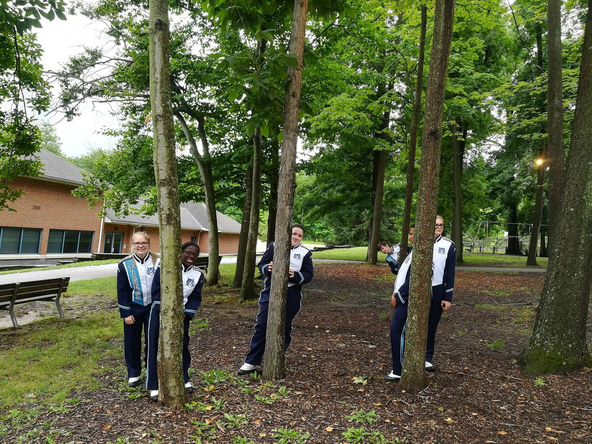 THS Marching Band Students hiding behind trees