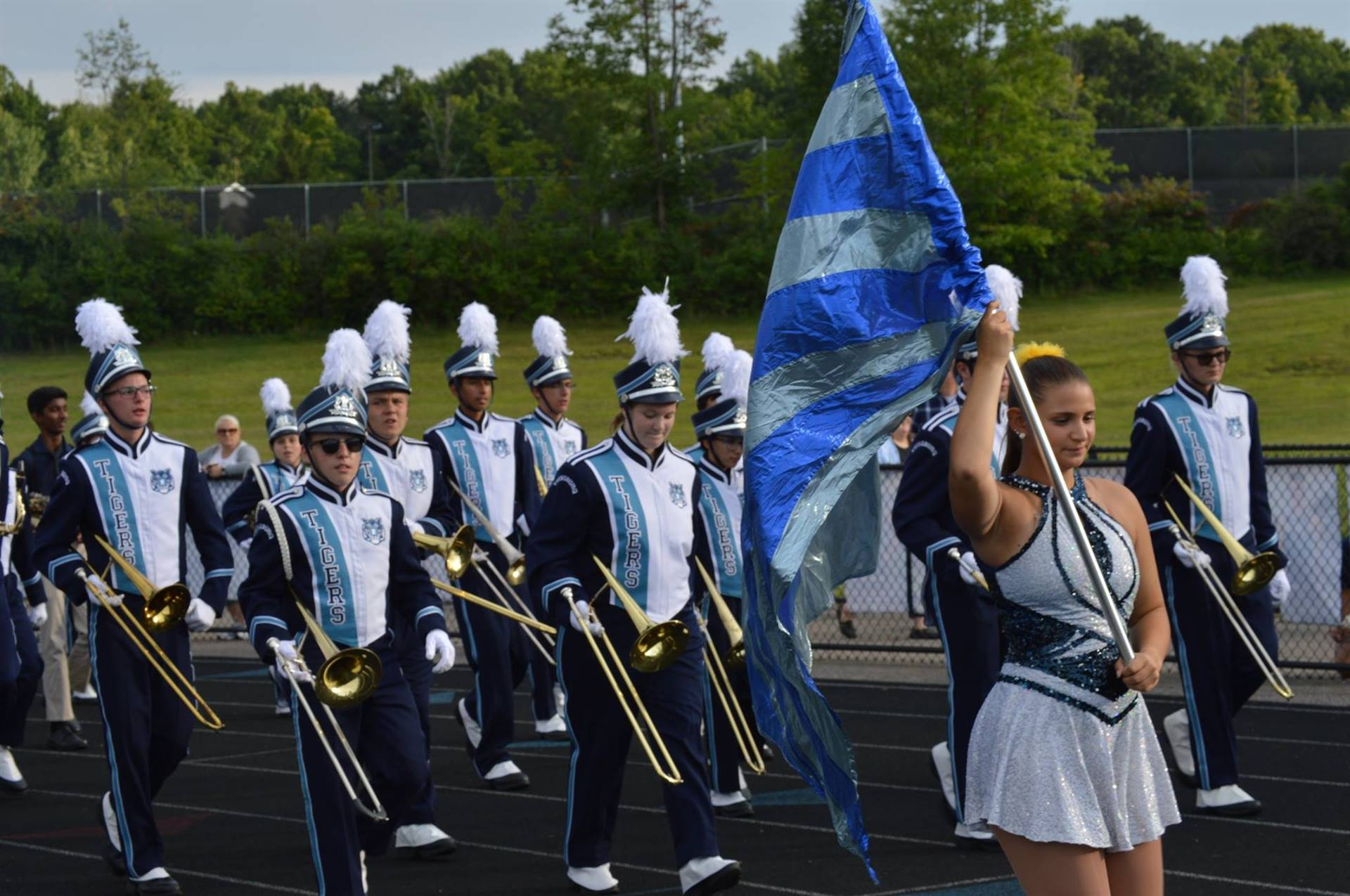 Marching Band Students and Drill Team marching before a game