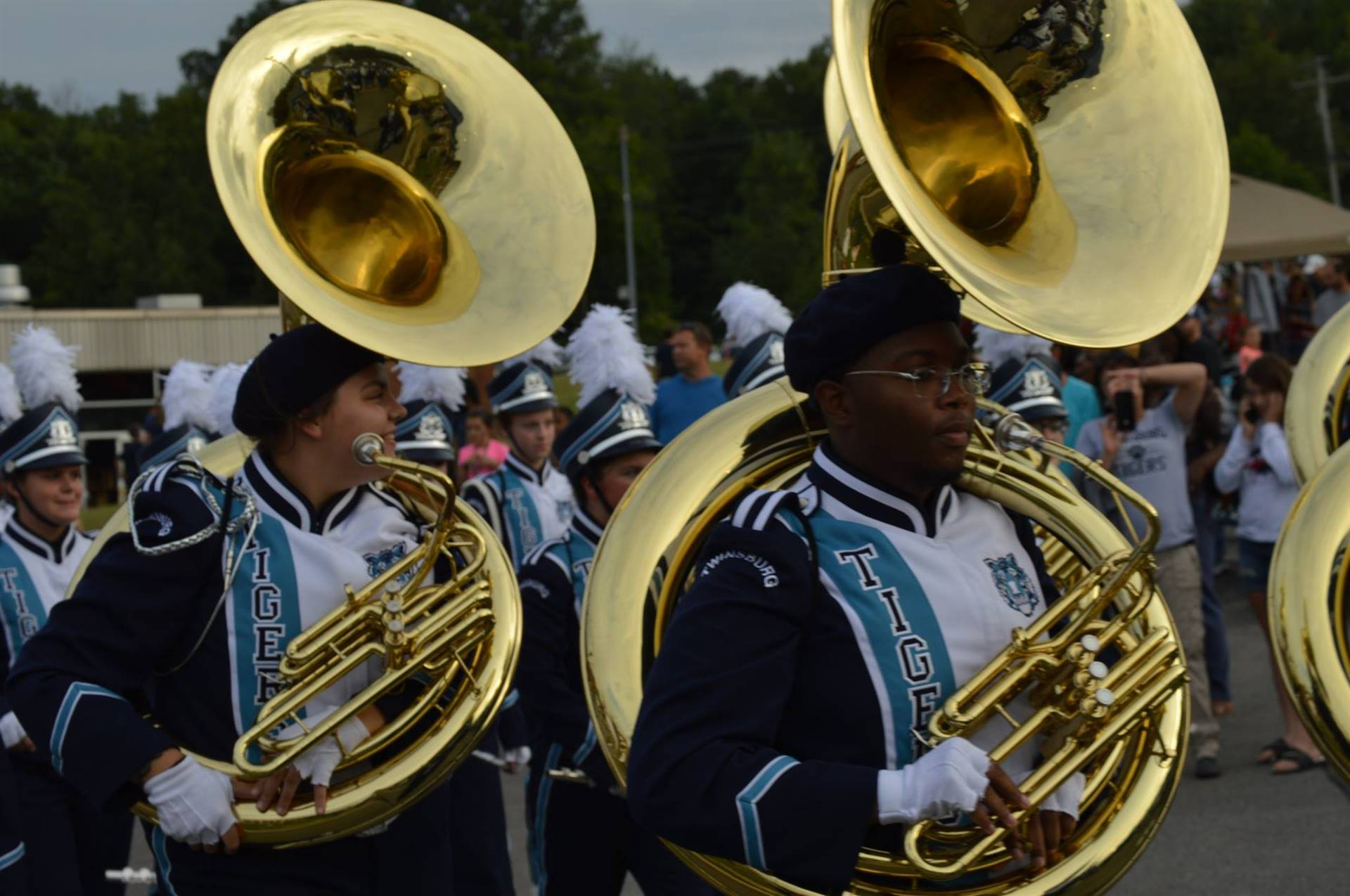 Tuba players marching in uniform