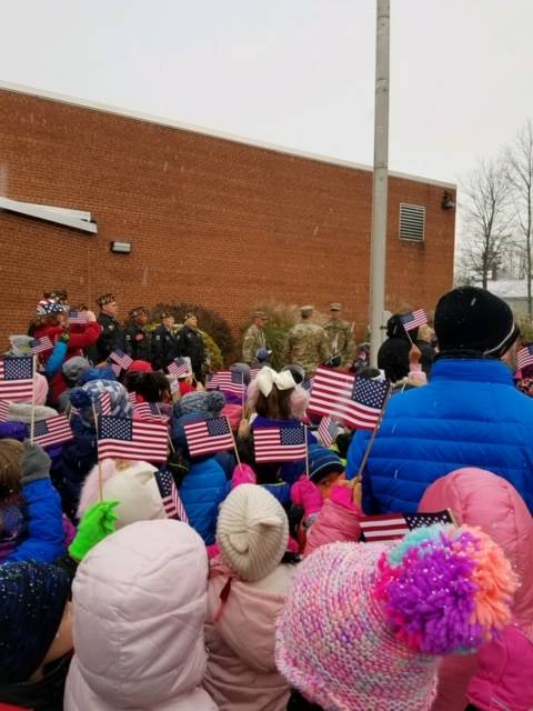 students staff and veterans standing around flag pole outside