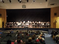 students performing in a band on stage