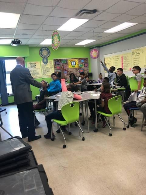 students sitting at desks listening to presenter