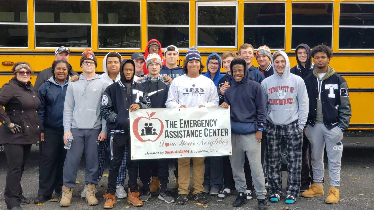 students standing in front of bus holding a sign which says The Emergency Assistance Center