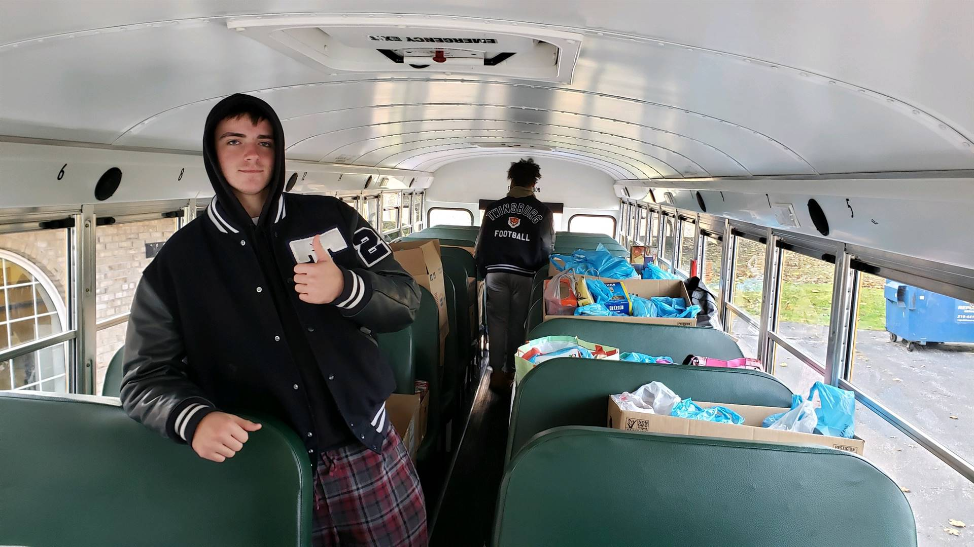 Students standing in a bus filled with nonperishable goods