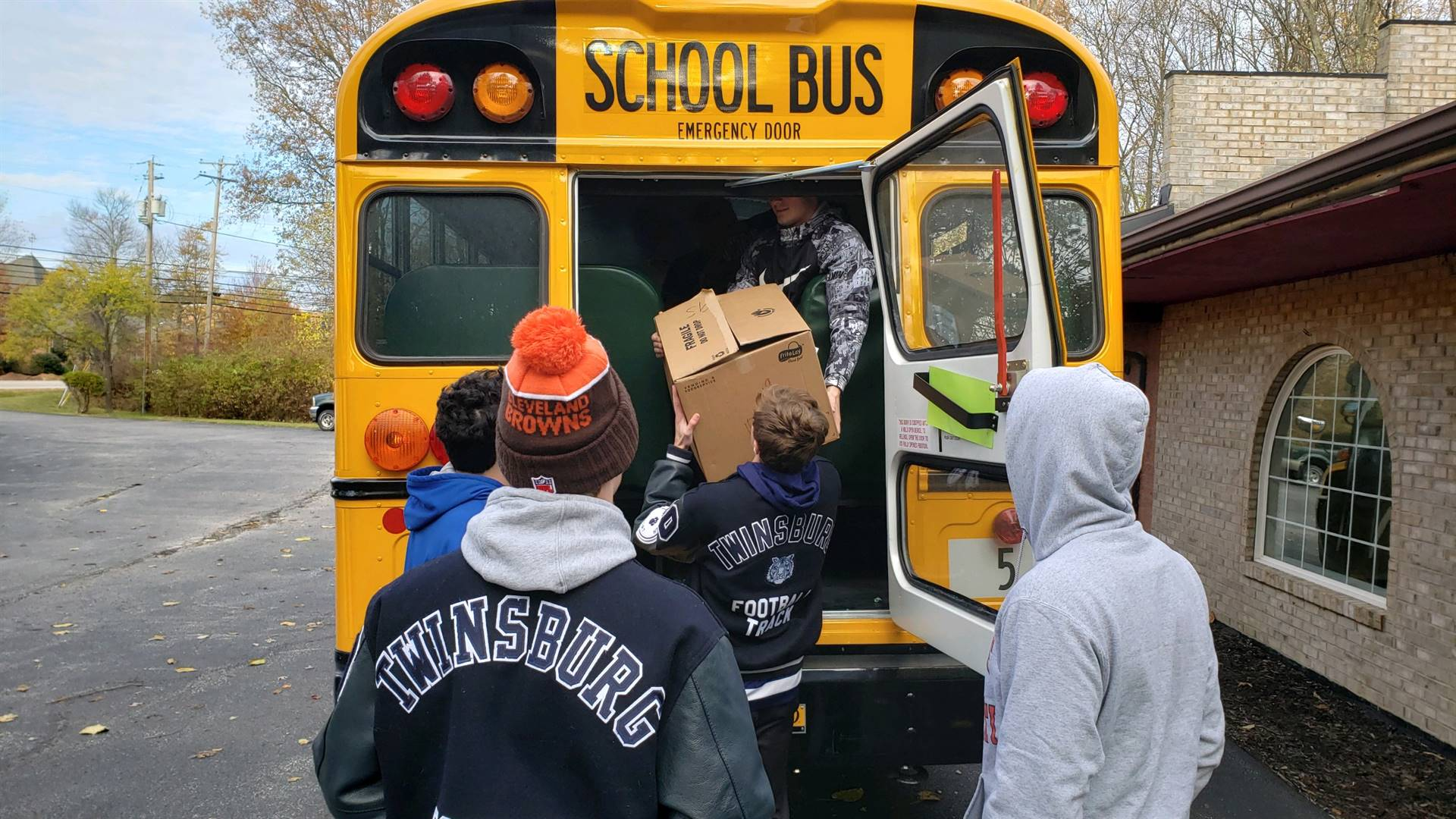 students loading nonperishable goods onto a bus through the back door