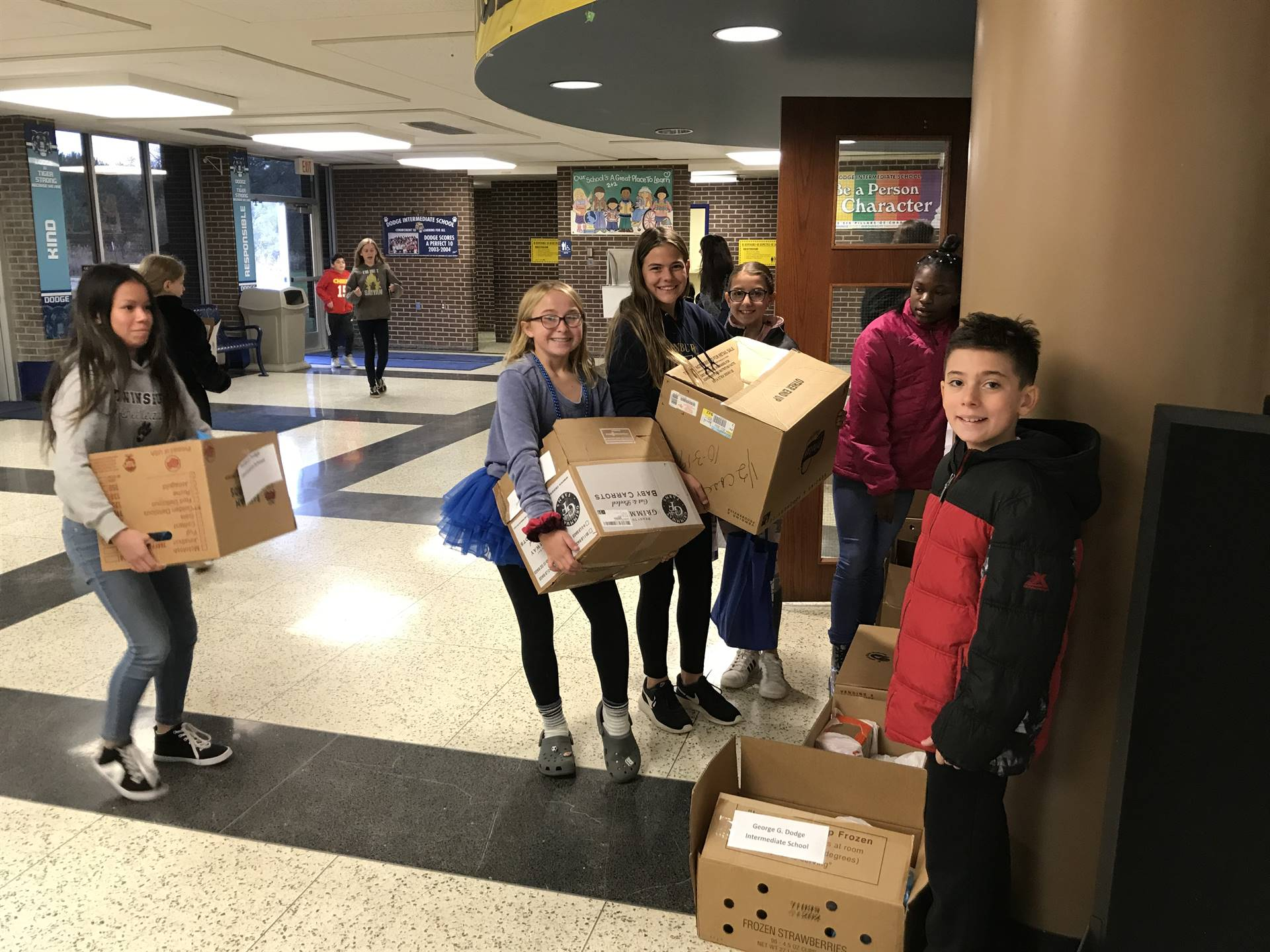 students carrying boxes of nonperishable goods