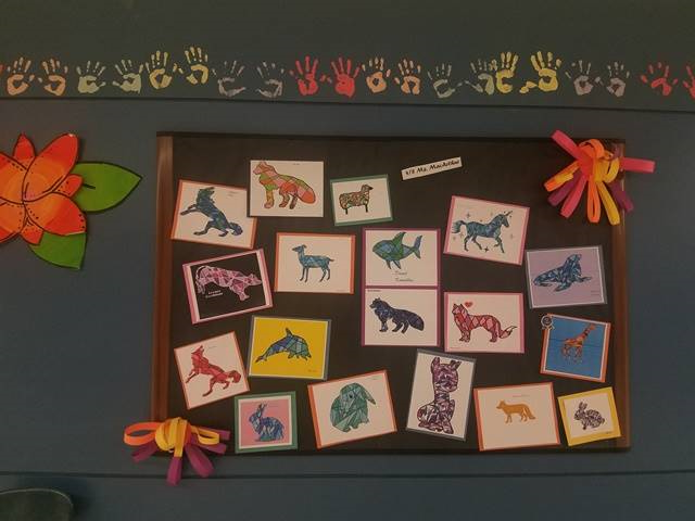 student artwork of animals on wall