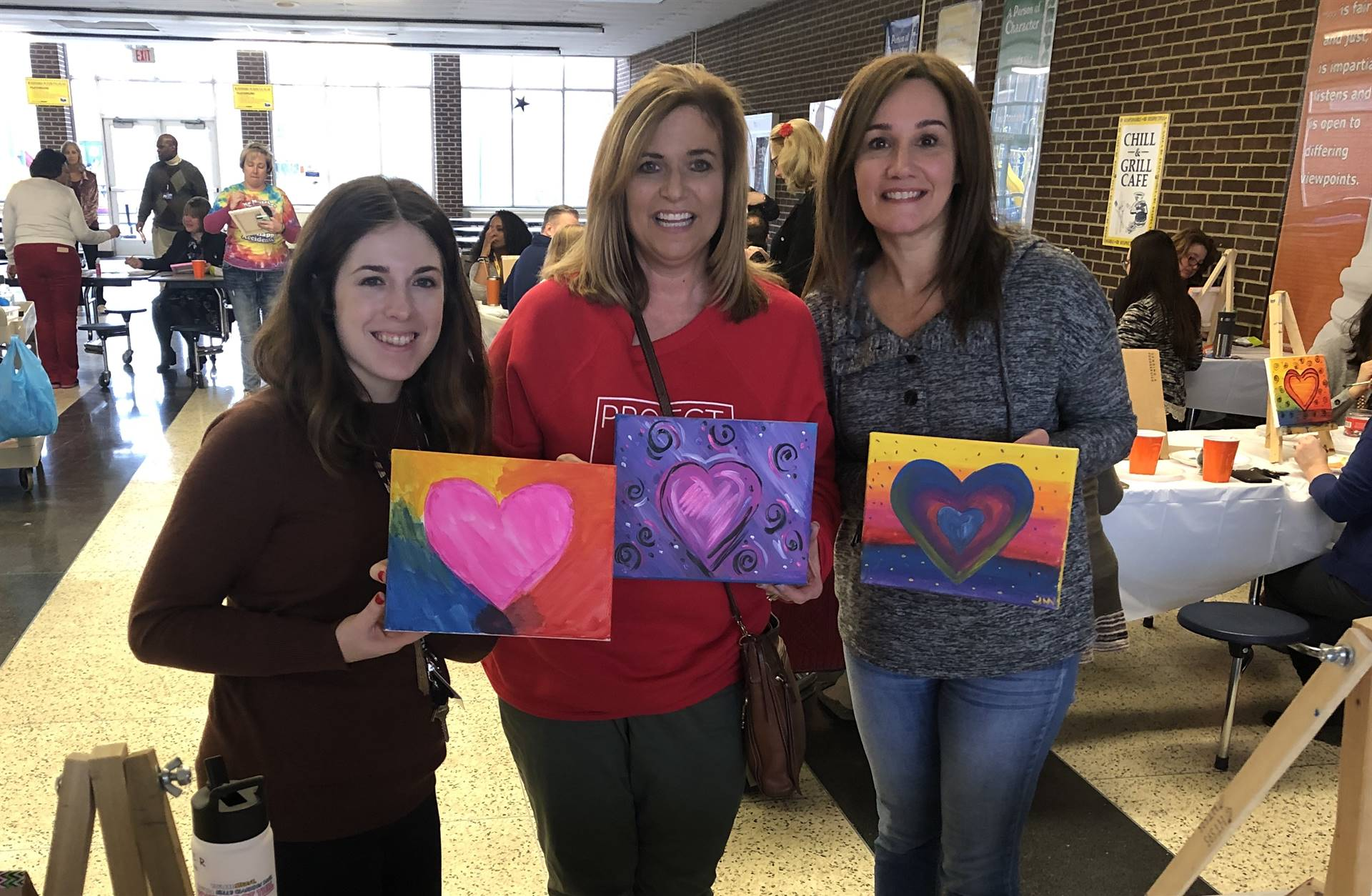 staff members holding their painting of a heart