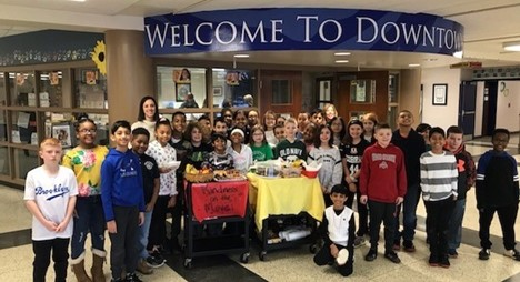 students standing around kindness cart filled with goodies